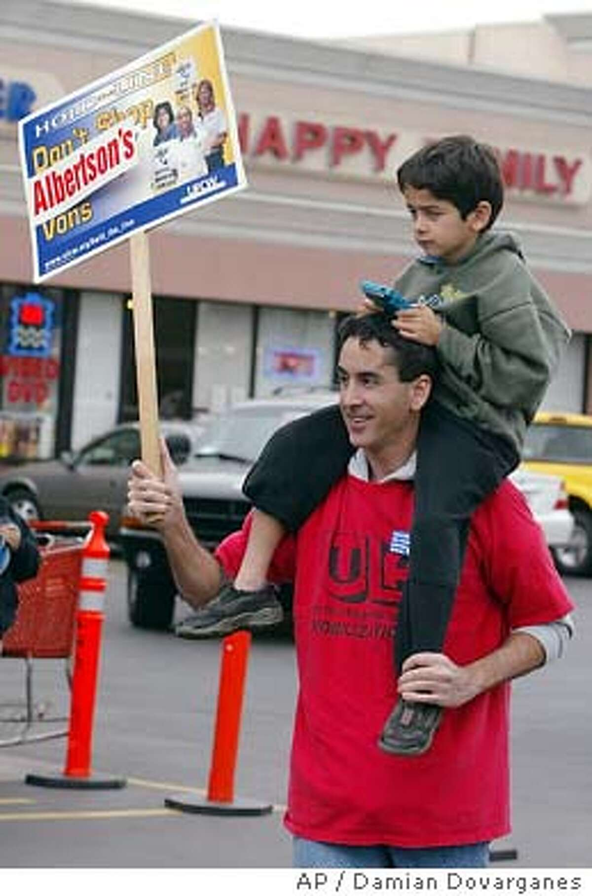 An unidentified worker and his son join the picketing line outside an Albertson's supermarket on the 133rd day of the strike-lockout, Saturday, Feb. 21, 2004, in Montebello, Calif. The strike-lockout began Oct. 11, a day after the roughly 70,000 United Food and Commercial Workers' union members voted to reject a labor contract offer from Albertsons Inc., Kroger Co., which owns Ralphs, and Safeway Inc., which runs Vons and Pavilions. Union leaders struck Vons and Pavilions, but Ralphs and Albertsons retaliated by locking out their workers. (AP Photo/Damian Dovarganes)