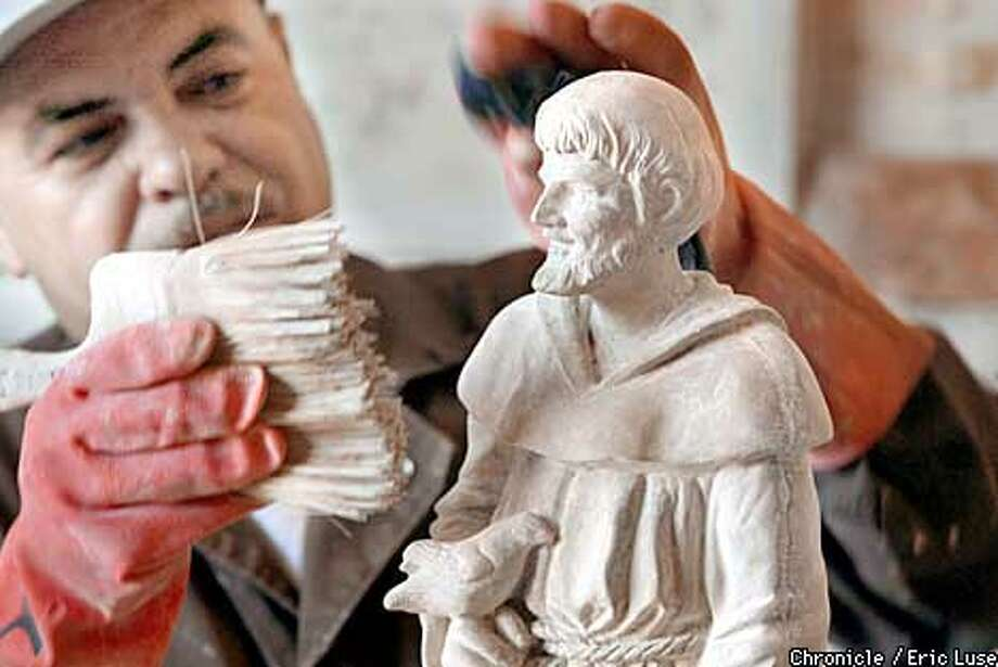 Daniel Garcia brushes off a newly finished statue at the Statue Factory in Brisbane. After this it will be painted and sealed.  BY ERIC LUSE/THE CHRONICLE Photo: ERIC LUSE