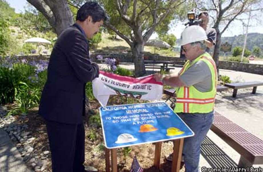 Randell Iwasaki (left), acting district director of the California Department of Transportation, and Caltrans worker Mario Conti unveil a memorial sign in honor of Caltrans workers who have lost their lives on the job. Chronicle photo by Darryl Bush
