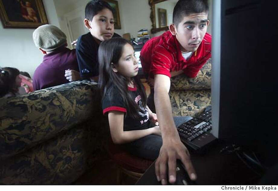 Gus Buenrostro, 18, (rt) shows his cousins Ricky Garibay, 10, and Elle Garibay, 9, how to play games on the new computer Habitat for Humanity installed in their Redwood City home Saturday. Habitat for Humanity's Rolison Road project in Redwood City will be the first to include computers for all of its new residents along with classes to help teach them how to utilize them. The 36-unit project opened its last phase in recent months but residents are still going through a lot of changes. They recieved computers this Saturday and will get tutoring and classes in the coming weeks and months to help them understand how to take advantage of the internet. This is the first time a Habitat Project includes computers for all of its low income residents.  Mike Kepka / The Chronicle Photo: Mike Kepka