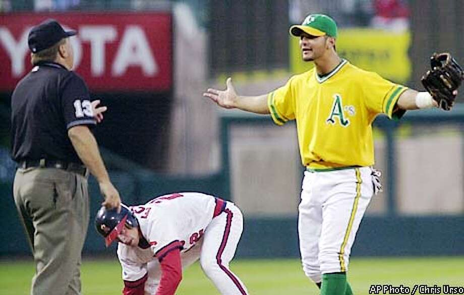 Oakland Athletics third baseman Eric Chavez argues a call with third base umpire Derryl Cousins after Anaheim Angels' David Eckstein was called safe for an RBI triple during the third inning Wednesday, July 24, 2002, in Anaheim, Calif. (AP Photo/Chris Urso) Photo: CHRIS URSO