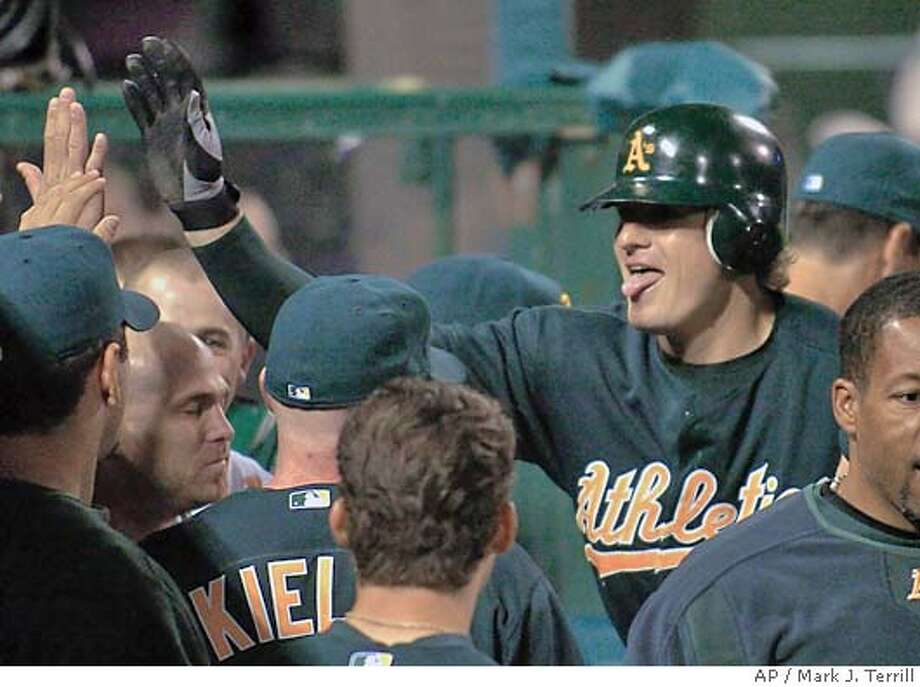 Oakland Athletics' Eric Byrnes, right, is congratulated by teammates after hitting a home run in the sixth inning against the Anaheim Angels on Friday night, April 16, 2004, in Anaheim, Calif. (AP Photo/Mark J. Terrill) Photo: MARK J. TERRILL