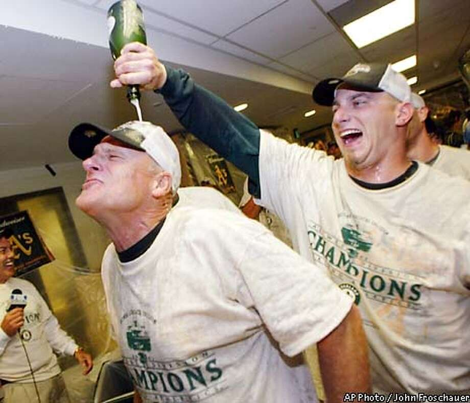Oakland Athletics manager Art Howe is doused with champagne by closing pitcher Billy Koch after beating the Seattle Mariners 5-3 to clinch the American League West championship in Seattle Thursday, Sept. 26, 2002. (AP Photo/John Froschauer) Photo: JOHN FROSCHAUER