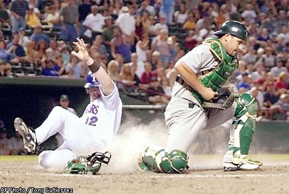 Oakland Athletics catcher Ramon Hernandez, right, cradles a ball in his glove to get the force against Texas Rangers' Hank Blalock (12) in the ninth inning holding off a late charge by the Rangers in the 3-2 Athletics win, Friday Sept. 27, 2002, at the Ballpark in Arlington, Texas. (AP Photo/Tony Gutierrez) Photo: TONY GUTIERREZ