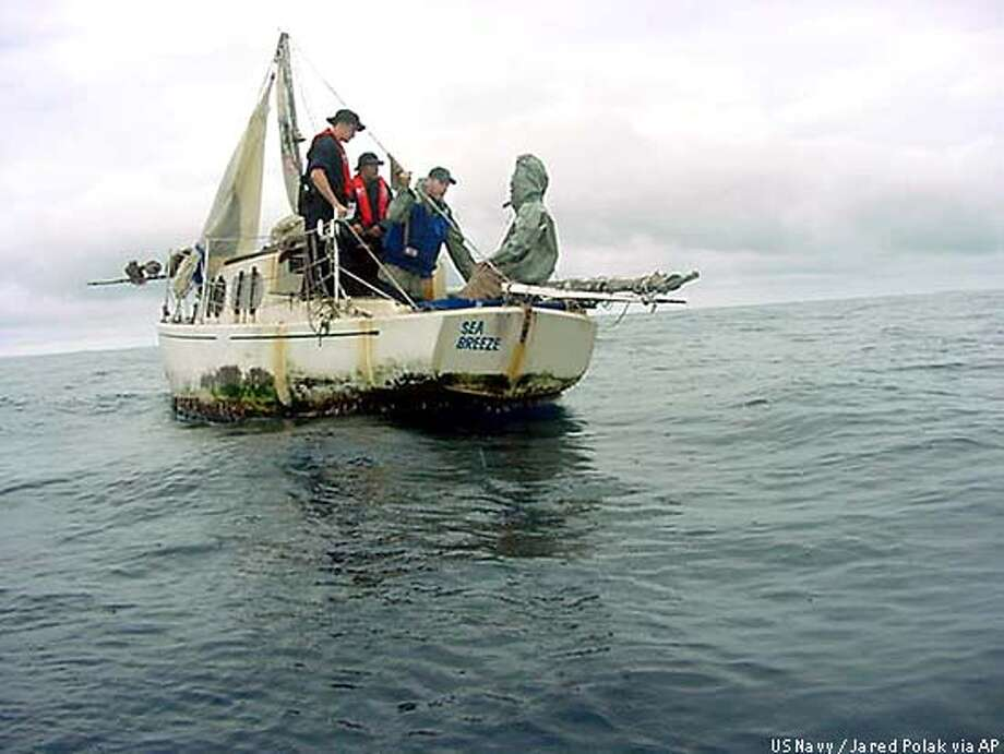Sailors from the U.S. Navy frigate McClusky speak to Richard Van Pham, right, aboard Pham's sailboat Sept. 17, 2002, after they found him adrift off the coast of Costa Rica. Van Pham was rescued after being adrift aboard his damaged sailboat at sea for more than three months, keeping himself alive by catching fish, seabirds and turtles for food. (AP Photo/U.S. Navy via The San Diego Union-Tribune, Jared Polak) Photo: JARED POLAK