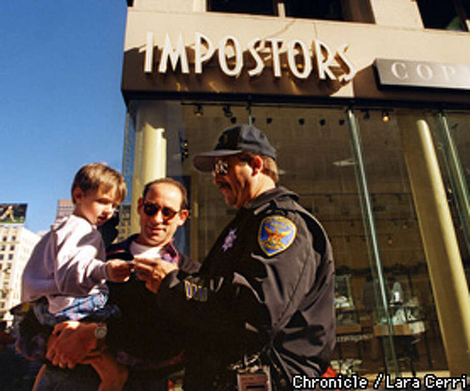 "MACYS BOMBING/01DEC97/MN/LC: SFPD Joe Kirley is part of ""Operation Safe Shopper,"" which aims to protect the shoppers in the Union Street area. Kirley, gives out stickers to shopper Sam (age 3) being helded by father David Miller from Boston in front of the Union square store ""Impostors"" which was subject to arson fire, along with Macys, the last two day. Chronicle photo by Laura Cerri"