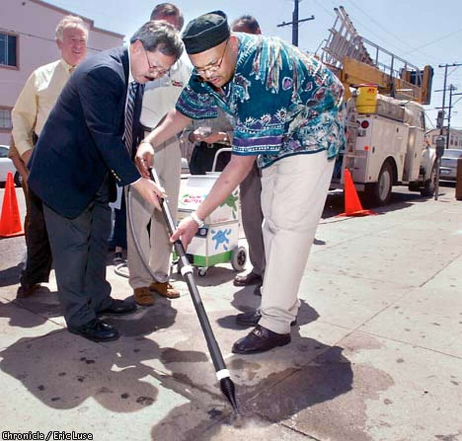 Ed Lee , Director of Public Works along with the Deputy Director of Operations Mohammed Nuru work on their technique with the Gum Buster. According to Nuru DPW is very excited about this new technology and will be recommending its use. BY ERIC LUSE/THE CHRONICLE Photo: ERIC LUSE