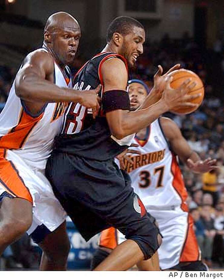 Golden State Warriors' Adonal Foyle, left, guards Portland Trail Blazers' Shareef Abdur-Rahim (33) during the first half Friday, Feb. 20, 2004, in Oakland, Calif. At right is Warriors' Nick Van Exel (37). (AP Photo/Ben Margot) Photo: BEN MARGOT