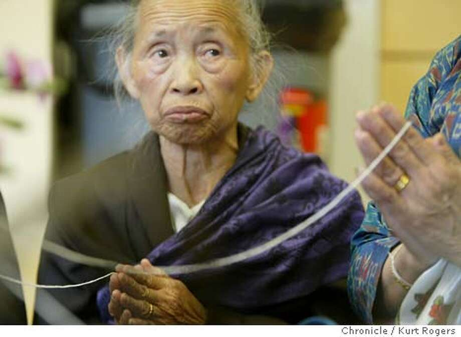 Chanthy Ounkeo holds a string that later is cut up and tied around the wrists of the people attending for good luck.  Laotian New Year's celebration in its new facility The Curry Senior Center in San Francisco seniors including Laotian refugees and Cambodians who survived the Cambodian Holocaust gathered to celebrate the event. Kurt Rogers /The Chronicle Photo: Kurt Rogers