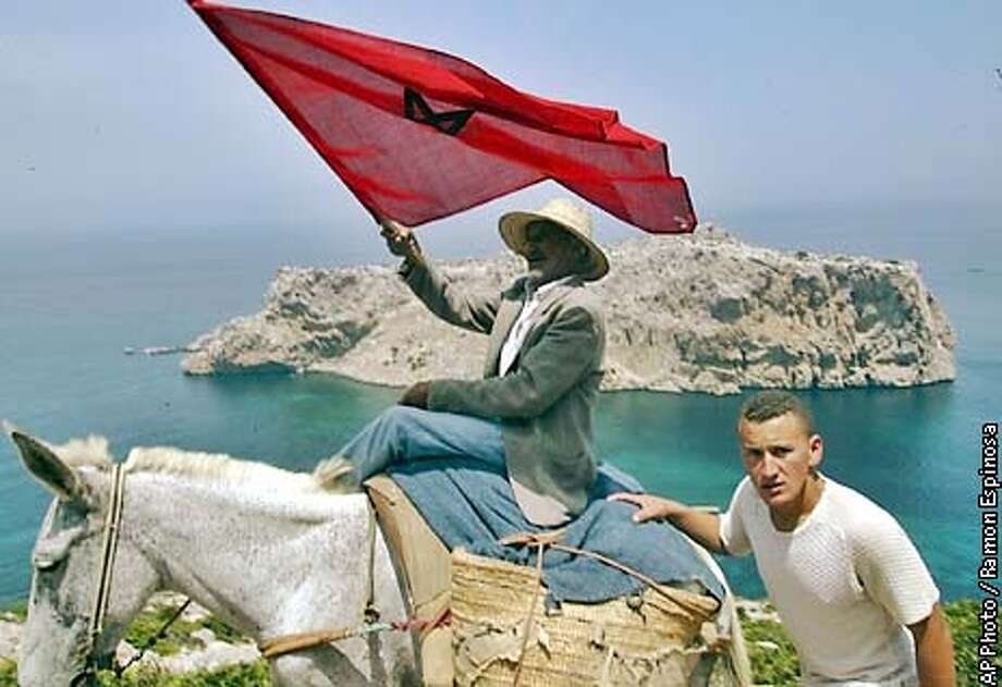 A Moroccan man waves a flag as he rides along the coast near the village of Belyounech, Morocco, in front of the island that Spain calls Perejil and Morocco calls Leila, Saturday, July 20, 2002. Spanish forces are still holding the Island after expelling Moroccan soldiers last Wednesday. (AP Photo/Ramon Espinosa) Photo: RAMON ESPINOSA