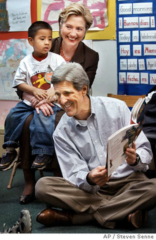 Sen. John Kerry reads as Sen. Hillary Rodham Clinton, D-N.Y., holds a child at a Manhattan preschool. Associated Press photo by Steven Senne
