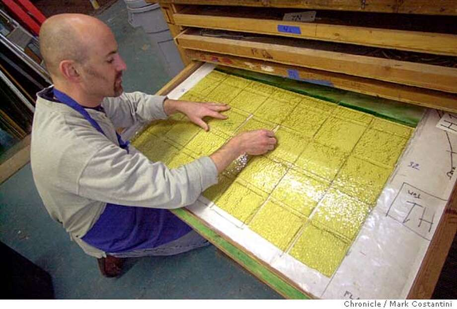 PNHISTORY20_0055.JPG Photo taken on 2/13/04 in Emeryville.  Artisan Tom Lehnartz looks over newly cleaned glass in a flat drawer.  Picture of stained glass artisans working on restoration of 3 1/2 foot -by 3 1/2-foot stained glass panels for skylight at San Mateo County History Museum. there are a total of 55 panels which once restored will be replaced in the ceiling of courtroom A, the centerpiece of the museum renovation. this is for a peninsula friday story for Feb 20 about the museum's renovation project and recent award of $1.1 million toward the project. Assignment location is the stained glass studio in Emeryville  CHRONICLE PHOTO BY MARK COSTANTINI Photo: MARK COSTANTINI