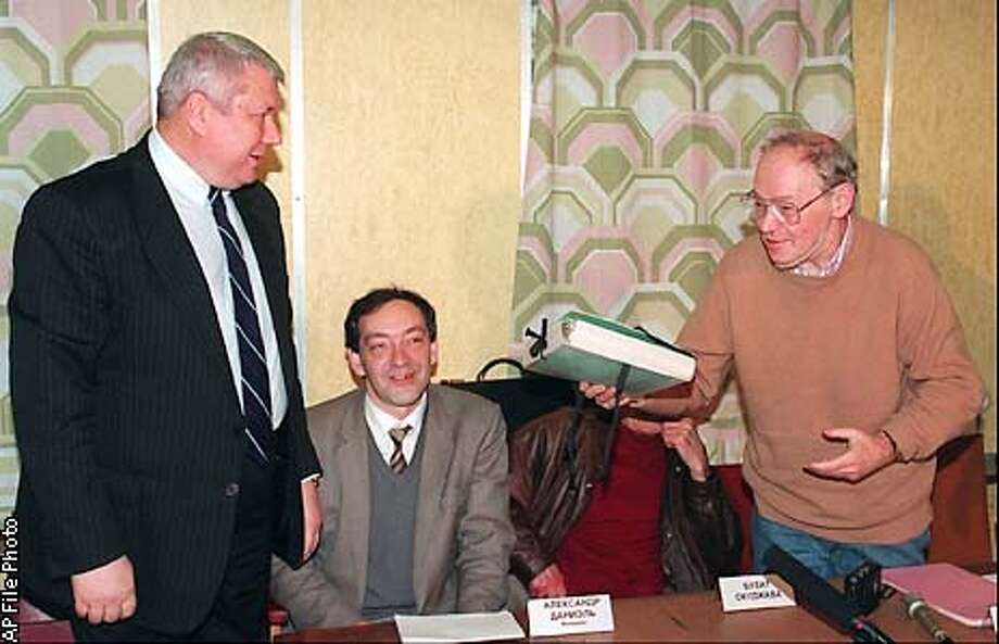 ** FILE ** Former dissident Alexander Ginzburg, right, holds a folder containing selected documents from Ginzburg's KGB files given him by Federal Security Service (FSB) archive's head Vladimir Vinogradov, in Moscow, on Oct. 17, 1995. Historian of the Memorial human rights group, Alexander Daniel, sits at center. Ginzburg - persecuted and jailed by Soviet authorities for starting the self-publishing movement that drove the dissident movement for decades - died Friday, July 19, 2002 in Paris, according to Russian news reports. He was 65. (AP Photo/Sergei Karpukhin) Photo: SERGEI KARPUKHIN