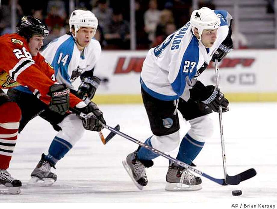San Jose Sharks' Niko Dimitrakos (23) skates the puck up the ice as Chicago Blackhawks' Mark Bell (28) tries to steal it and Sharks' Jonathan Cheechoo (14) follows during the first period Thursday, Feb. 19, 2004, in Chicago. (AP Photo/Brian Kersey) Photo: BRIAN KERSEY