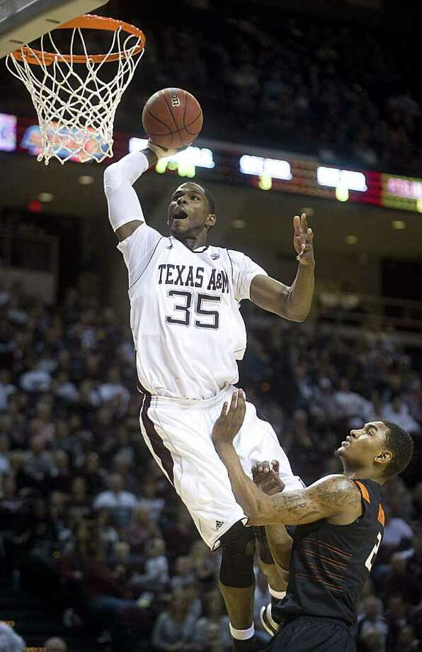 Texas A&M's Ray Turner dunks the ball over Oklahoma State's Le'Bryan Nash uring the first half of an NCAA college basketball game at Reed Arena in College Station, Texas, Saturday, Jan. 28, 2012.  (AP Photo/Bryan-College Station Eagle, Stuart Villanueva) Photo: Stuart Villanueva, Associated Press / Bryan College Station Eagle
