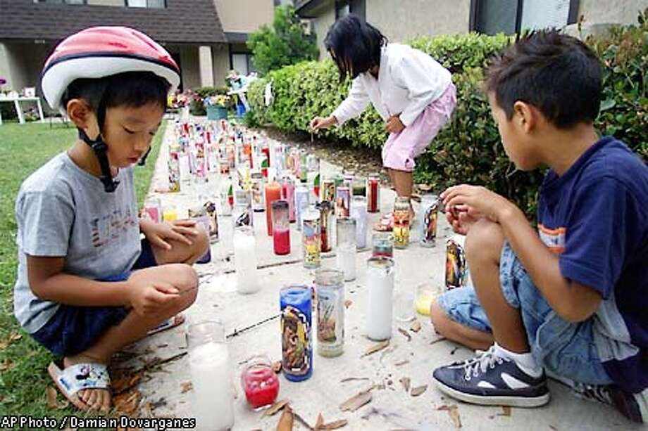 Neighbors Eugene Chang 6, left, Jazmine Chang 7 ,center, and Jude Labastida 8, use sticks to keep candles set for their friend Samantha Runnion lit outside her home Friday, July 19, 2002 in Stanton, Calif. Five-year-old Samantha was kidnapped last Monday from outside her home. A man identified as Alejandro Avila has been arrested in connection with the investigation of the kidnapping and killing of Runnion. (AP Photo/Damian Dovarganes) Photo: DAMIAN DOVARGANES