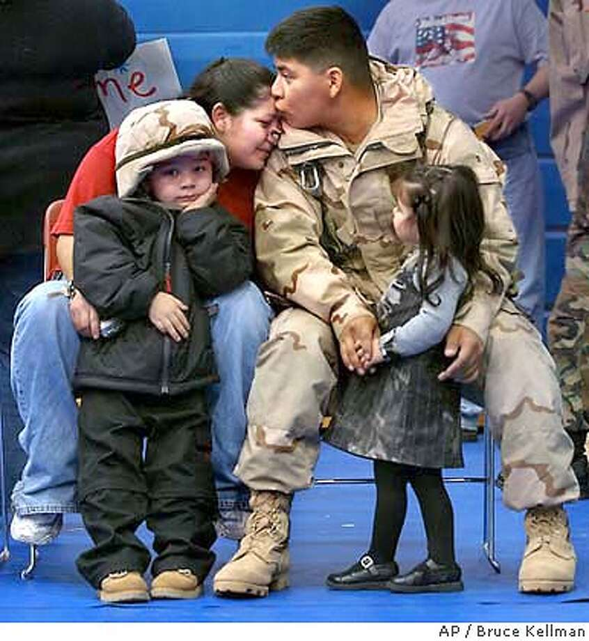 U.S. Army Spc. Mauricio Luna, with the 864th Engineer Battalion is reunited with his daughter Julia, right, wife Vanessa and son Mauricio, Thursday, Feb. 19, 2004, at Fort Lewis, Wash., after serving in Iraq. (AP Photo/The News Tribune, Bruce Kellman) STANDS ALONE U.S. Army Spc. Mauricio Luna, with the 864th Engineer Battalion, is reunited with his daughter, Julia (right), his wife, Vanessa, and his son, Mauricio, at Fort Lewis, Wash., after serving in Iraq. Photo: BRUCE KELLMAN