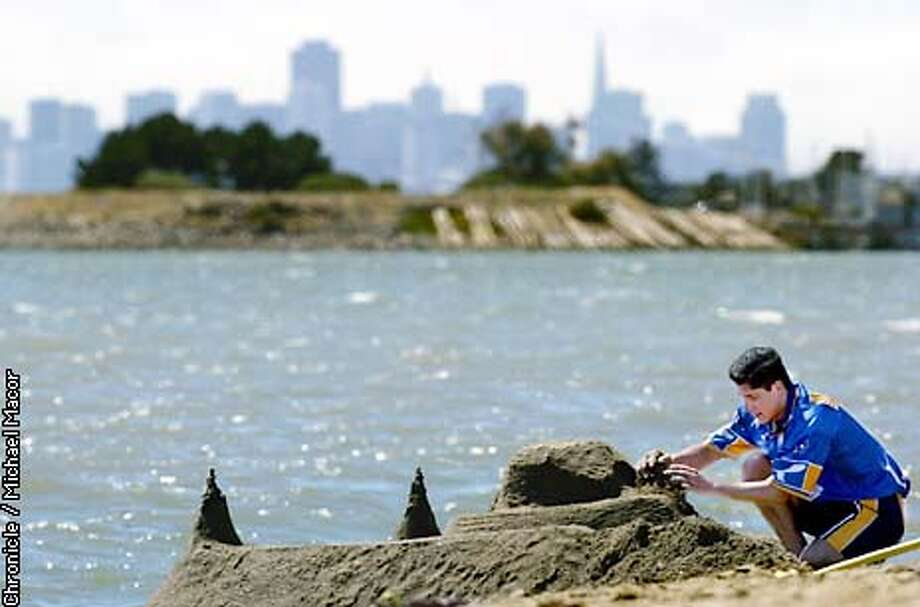 Jose Luis Gutierrez of Modesto builds a sand castle on the shore of SF Bay along Crown Beach in Alameda, with the skyline of San Francsico in the background. Gutierrez in town visitng relatives. by Michael Macor/The Chronicle Photo: MICHAEL MACOR