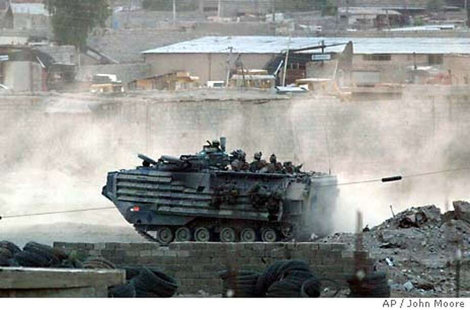 "A U.S. Marine amphibious assault vehicle moves towards a battle in Fallujah, Iraq Tuesday, April 13, 2004. Although an official ""ceasfire"" remains in place, Marines in Fallujah came under intense fire Tuesday and called for reinforcements. (AP Photo/John Moore) Photo: JOHN MOORE"