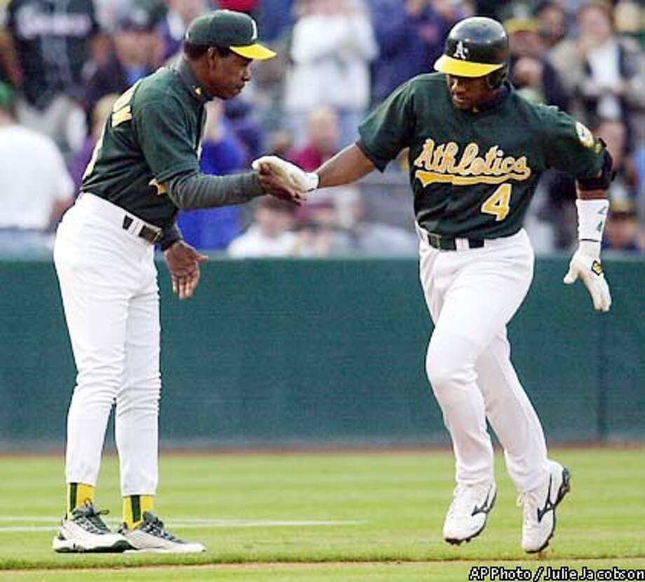 Oakland Athletics' Miguel Tejada, right, is congratulated by third base coach Ron Washington while rounding the bases after hitting a solo home run against the Anaheim Angels during the first inning Thursday, July 18, 2002 in Oakland, Calif. (AP Photo/Julie Jacobson) Photo: JULIE JACOBSON