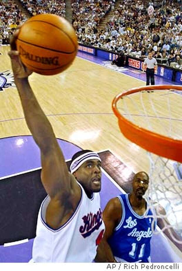 Sacramento Kings forward Chris Webber, left, dunks over Los Angeles Lakers forward Karl Malone, right, in the third quarter in Sacramento, Calif., Sunday, April 11, 2004. Webber scored a game-high 25 points to lead the Kings to a 102-85 win over the Lakers. (AP Photo/Rich Pedroncelli) Photo: RICH PEDRONCELLI