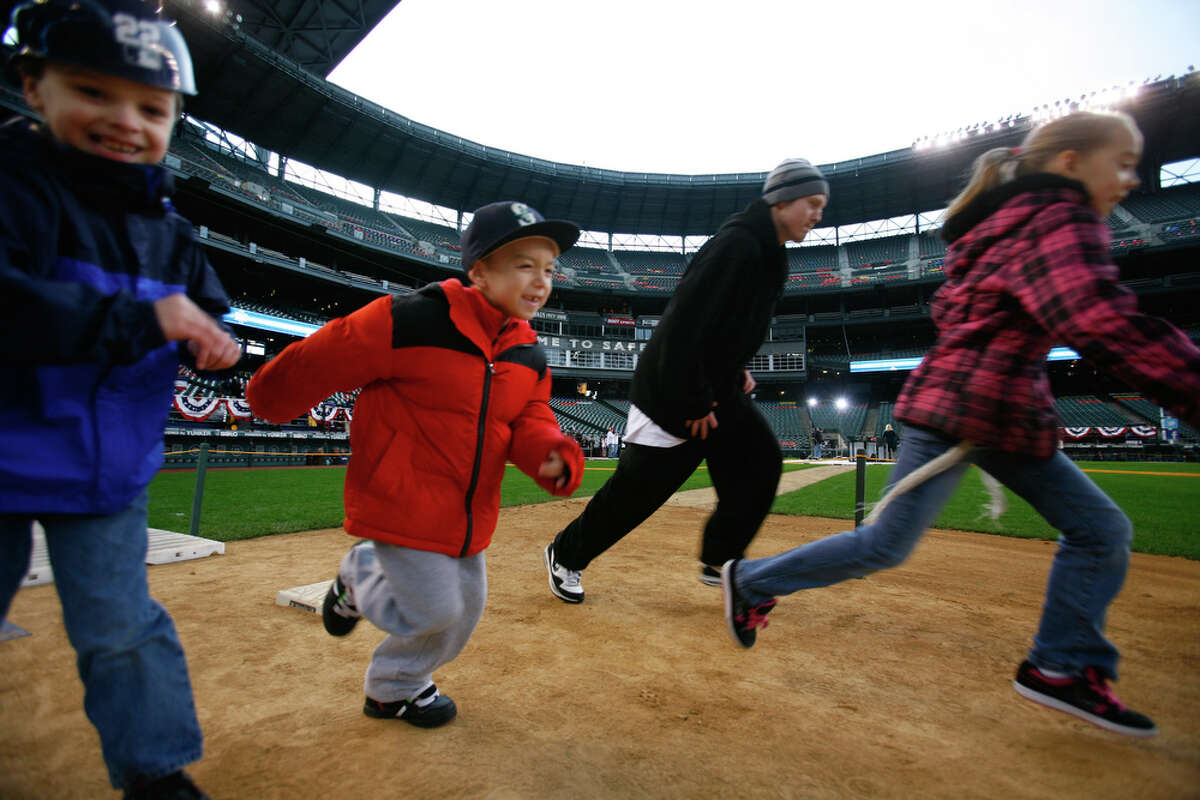 People run the bases during FanFest at Safeco Field on Saturday, Jan. 28, 2012. The 14th Annual Mariners FanFest continues on Sunday, Jan. 28, from 11am-4pm. The event features numerous activities for children and adults alike around the concourse. FanFest also lets attendees run the bases, play catch on the field, and do a virtual sportscast.