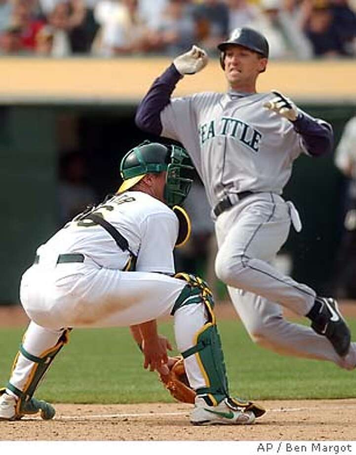 Seattle Mariners' John Olerud slides safely behind Oakland Athletics' catcher Damian Miller in the 10th inning Sunday, April 11, 2004, in Oakland, Calif. Olerud scored on a hit by Willie Bloomquist.Seattle defeated Oakland 9-4 in 10 innings to win their first game of the year.(AP Photo/Ben Margot) Photo: BEN MARGOT
