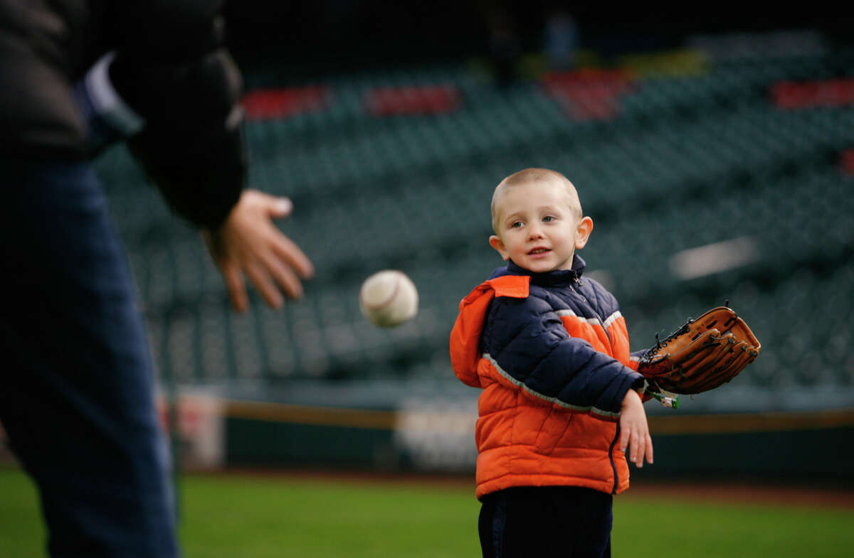Trevon Butikofer, 3, throws a ball to his mother during FanFest at Safeco Field on Saturday, Jan. 28, 2012. The 14th Annual Mariners FanFest continues on Sunday, Jan. 28, from 11am-4pm. The event features numerous activities for children and adults alike around the concourse. FanFest also lets attendees run the bases, play catch on the field, and do a virtual sportscast.
