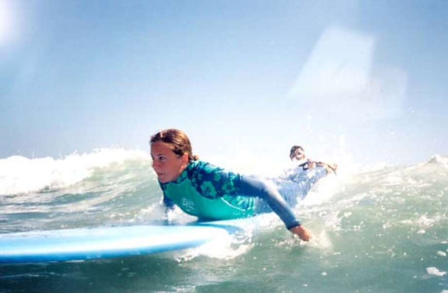 A student at Surf Diva near La Jolla paddles into one of her first waves, ready to pop up and get stoked.