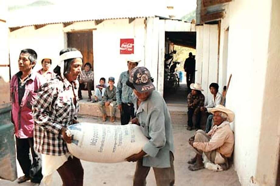 Raramuri Indian men in Yerba Buena, Mexico, unload relief supplies brought by the Apoyo Tarahumara aid group. Photo by Reese Erlich, special to the Chronicle