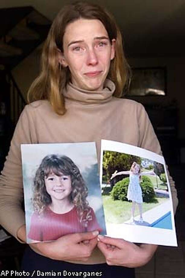 Erin Runnion expresses her grief Tuesday, July 16, 2002, as she shows two photos of her daughter Samantha Runnion, 5, who was abducted, Monday, July 15, 2002, outside her home in Stanton, Calif. Samantha was playing a board game with her 5-year-old friend, Sarah Ahn, when a man drove up in a light green Honda, said Jim Amormino, a spokesman for the Orange County Sheriff's Department. The man got out of his car next to the girls and asked them for help finding his dog, Amormino said. Witnesses told deputies Samantha talked to the man before he grabbed her and drove off. (AP Photo/Damian Dovarganes) Photo: DAMIAN DOVARGANES