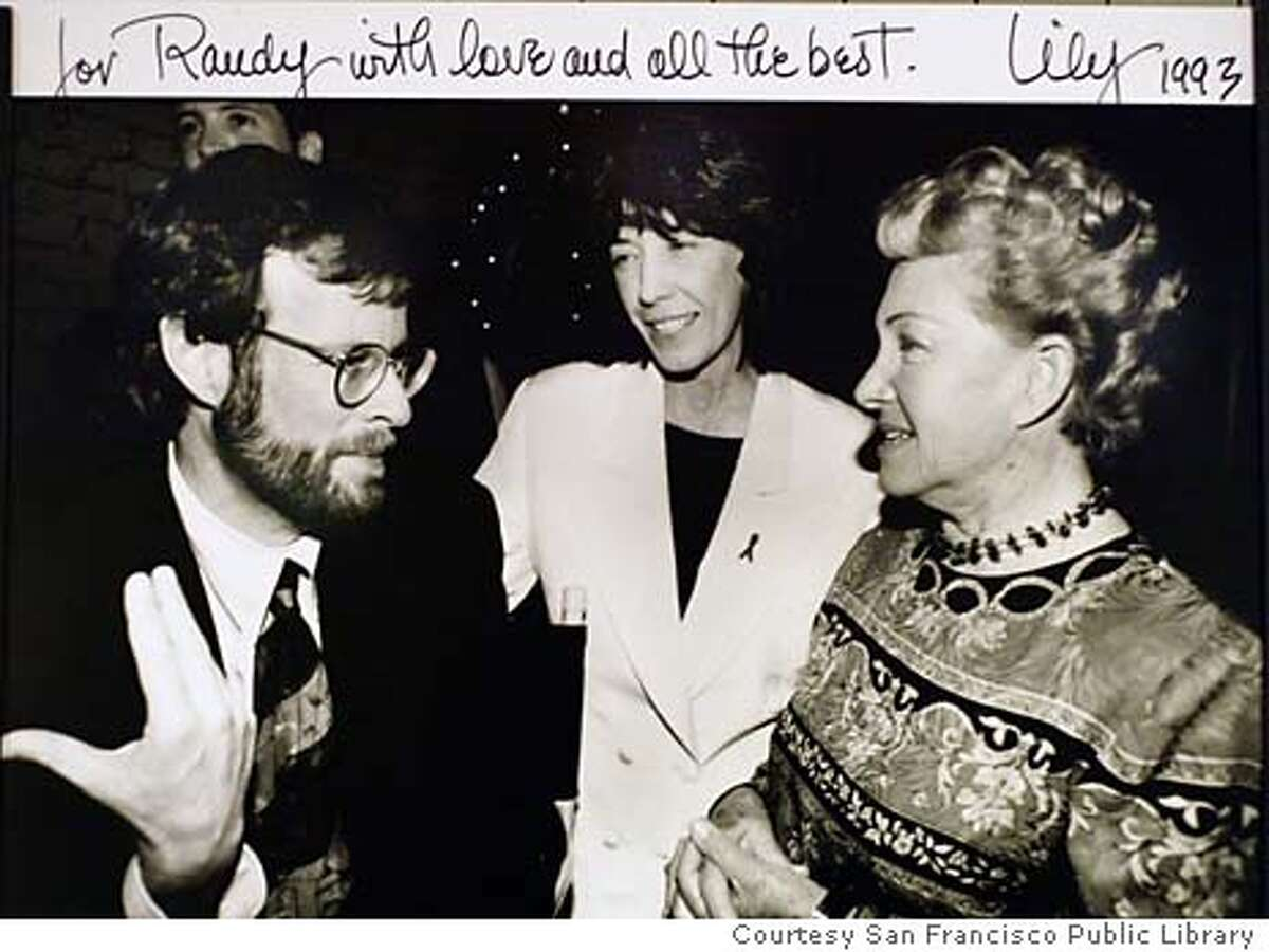 Former San Francisco Chronicle staff writer and author of The Band Plays On, Randy Shilts, talks with comedian Lily Tomlin and a unidentified women in this file photo dated 1993 Photo Curtasy San Francisco Library and Lily Tomlin. Editors Note: We only have permition from the Libraray to use this image. They have no idea who the photographer was or who may own the rights to the image.