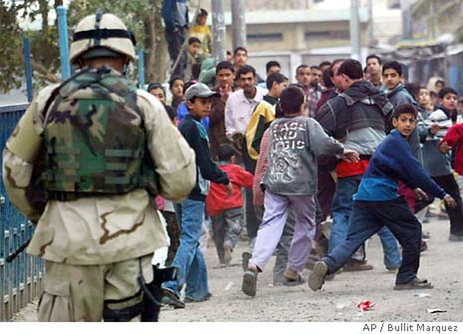 US Military Police chase away Iraqi onlookers, as they secure the Khadimiya primary school compound in Baghdad, Iraq, after school children, playing during their recess period, accidentally detonated a grenade, Monday Feb. 16, 2004 which killed one child and wounding four others. (AP Photo/Bullit Marquez) Photo: BULLIT MARQUEZ
