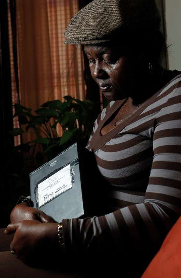 Kim Young, holding the ashes of her uncle, Herman Young, is upset that she was never told her uncle was assaulted in jail by a deputy. Photo: Karen Warren / © 2012  Houston Chronicle