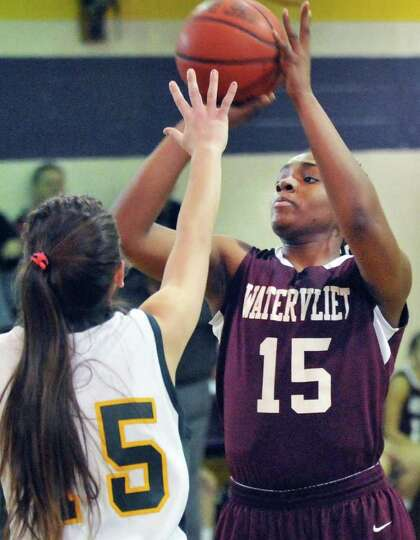 Watervliet's #15 Lashano Tolliver, at right, gets a shot off against Ravena's #15 Hope Rebeor during