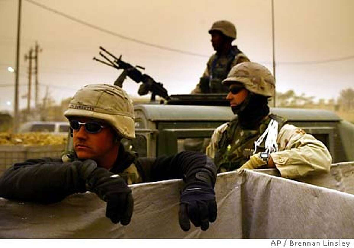 As a sandstorm moves in over central Iraq, U.S. soldiers man a checkpoint near the Iraqi Police Academy complex, in Baghdad, Iraq, Sunday, Feb. 15, 2004. (AP Photo/Brennan Linsley)