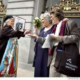 People getting married at San Francisco City Hall. SHOWN: Sandra Hollingsworth (C) and Robyn Lock (R) of Oakland exit City Hall to the cheers of the crowd, while Helene Hildegard (L) attempts to make them see the truth her way by giving them a religious medal and brandishing a picture of Jesus Christ. The gay couple was most polite, as was the religious zealot. Katy Raddatz / The Chronicle