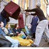 [filename}  Hillary Hartley of San Francisco grabs a inflatable bedmat for a couple waiting in line to be wed on Monday at City Hall. Underneath the bed mat are from left to right: Molly Hollis, Erin Lewis and Pace Reagan who arrived from Austin yesterday (Sat) and watch from underneath their blankets on the sidewalk by City Hall. Hollis and Lewis are planning to be married and Reagan came out to witness. Couples line up in front of City Hall on Sunday night to be first in line to be married on 2/15/04 in San Francisco, CA. Lea Suzuki/San Francisco Chronicle