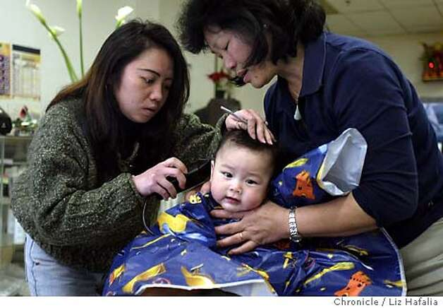 Sebastian Lam, 6 months old, getting his first haircut from Margaret Ng (left) at Venezuela Hair Salon--704 Larkin St.. Sebastian's grandmother, Maria Lam (right), holding her grandson's head. A two block area around Larkin St. has recently been designated as Little Saigon. Shot on 2/3/04 in San Francisco. LIZ HAFALIA / The Chronicle Photo: LIZ HAFALIA
