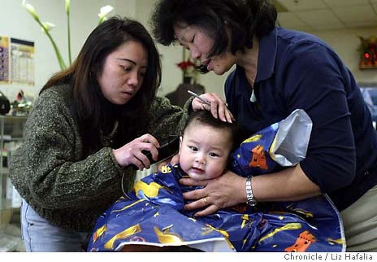 Sebastian Lam, 6 months old, getting his first haircut from Margaret Ng (left) at Venezuela Hair Salon--704 Larkin St.. Sebastian's grandmother, Maria Lam (right), holding her grandson's head. A two block area around Larkin St. has recently been designated as Little Saigon. Shot on 2/3/04 in San Francisco. LIZ HAFALIA / The Chronicle