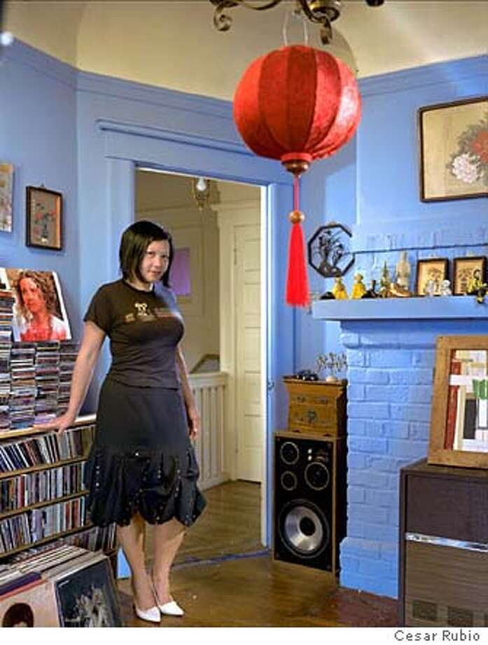 Windy Chien poses in her music room amid her CDs and record albums. The red silk shade is from a recent trip to Taiwan. Photo by Cesar Rubio