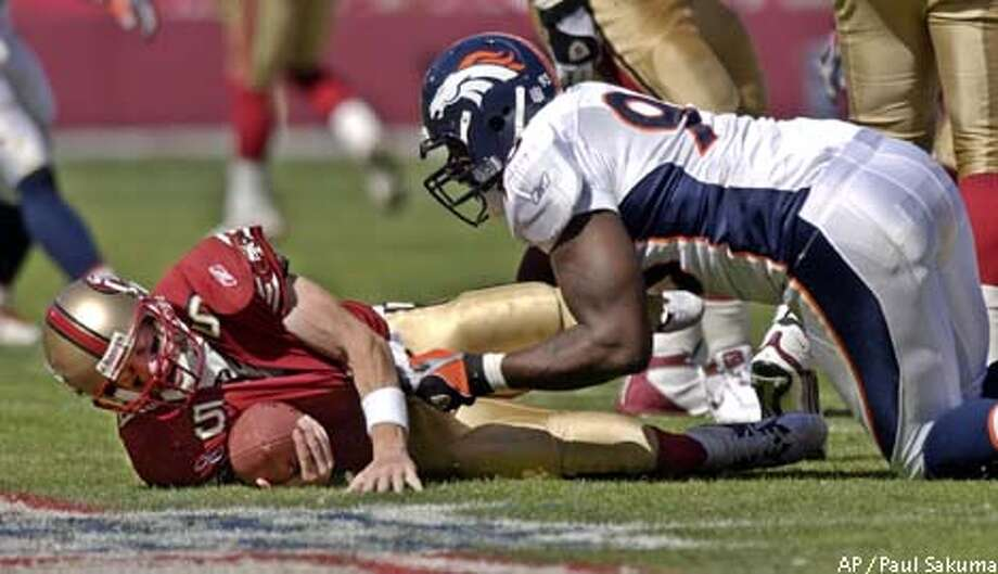 San Francisco 49ers quarterback Jeff Garcia is sacked for a loss by Denver Broncos defensive end Trevor Pryce in the third quarter, Sunday, Sept. 15, 2002 in San Francisco. The Broncos defeated the 49ers 24-14. (AP Photo/Paul Sakuma) Photo: PAUL SAKUMA