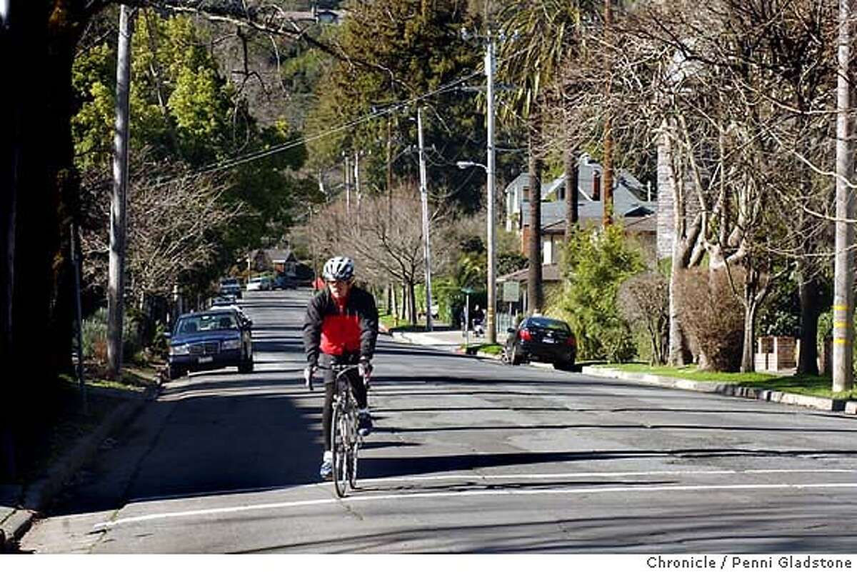 A bike rider begins his turn on this tree lined street. home values dramatically affected by school districts. house at 19 bolinas Ave. ross, Houses across the street sell for less which is in San Anselmo. Photo taken on 02/09/04 in Ross, CA. Photo By PENNI GLADSTONE / The San Francisco Chronicle