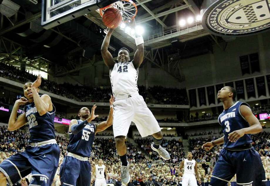 Pittsburgh's Talib Zanna (42) dunks after getting through Georgetown's Mikael Hopkins (3), Jabril Trawick (55) and Otto Porter (22) in the first half of the NCAA college basketball game on Saturday, Jan. 28, 2012, in Pittsburgh. (AP Photo/Keith Srakocic) Photo: Keith Srakocic