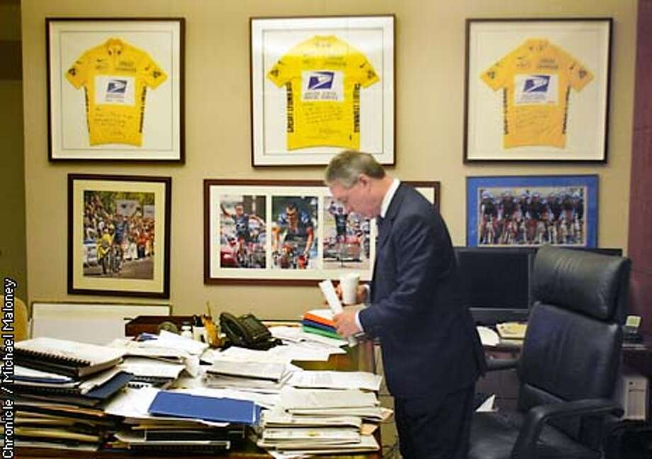 Weisel checks his morning mail beneath the three jerseys.  Thom Weisel, CEO of the SF investment firm Thomas Weisel Partners has his office wall full of Lance Armstrong photos including 3 framed yellow jerseys presented to him by his friend Lance Armstrong.Weisel now needs to make room for the 4th jersey. A profile on Weisel who is an accomplished cyclist himself and a huge success in the business world despite the tough economic times. CHRONICLE PHOTO BY MICHAEL MALONEY Photo: MICHAEL MALONEY