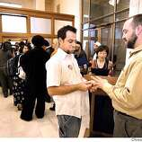 Mike Kabler, left, puts a ring on partner on finger of Kevin Fox, both of Oakland, during a marriage ceremony conducted by Assessor Mabel Teng, center, at City Hall as many same sex marriages are permitted for the first time at City Hall. Other ceremonies are taking place in the background. PHOTO BY DARRYL BUSH/CHRONICLE Event on 2/12/04 in San Francisco. DARRYL BUSH / The Chronicle