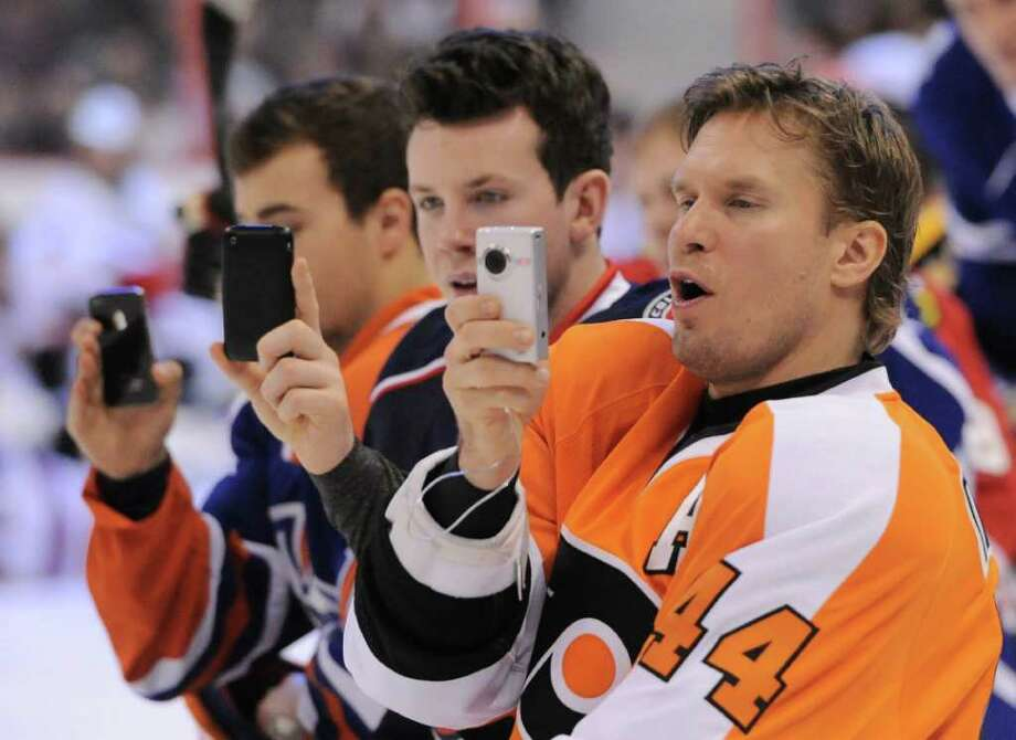 The Flyers' Kimmo Timonen, right, becomes an enthusiastic spectator as he photographs the hardest-shot event during Saturday night's NHL All-Star skills competition. Bruins defenseman Zdeno Chara won with a slap shot clocked at 108.8 mph. Photo: Sean Kilpatrick / The Canadian Press
