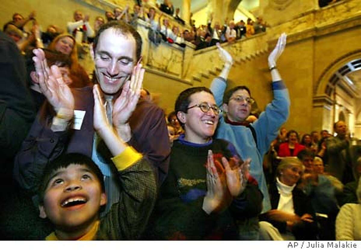 Greg Lipshitz of Newton, Mass., top left, applauds along with his son Rafael Gregory, 8, during a rally against the possible amendment to ban same-sex marriage, at the Statehouse in Boston, Tuesday, Feb. 10, 2004. At right are Nechama Katz, front, and her partner Serena Shapiro, of Boston. (AP Photo/Julia Malakie) Greg Lipshitz (left) applauds with his son Rafael Gregory at a rally supporting same-sex marriage at the Statehouse in Boston. At right are Nechama Katz (front) and her partner, Serena Shapiro.