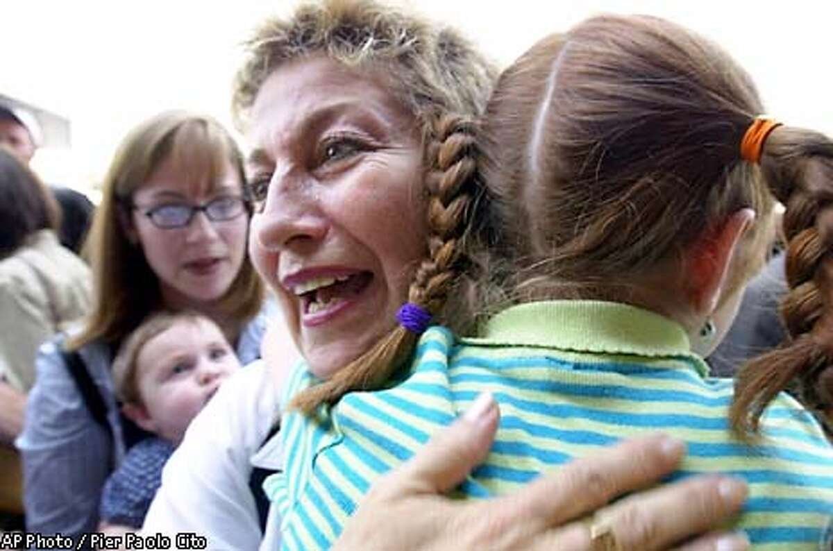 Nomi Malek, 55, welcomes her grandniece Tova, 7, as her daughter Tamar Rudy, 27, from Baltimore, Md., in the background, holds her daughter Michal, 8 months, after arriving at Tel Aviv's Ben Gurion's airport, Tuesday July 9, 2002. Defying Mideast violence, about 400 North Americans moved to Israel Tuesday to build new lives in the Jewish state. (AP Photo/Pier Paolo Cito)