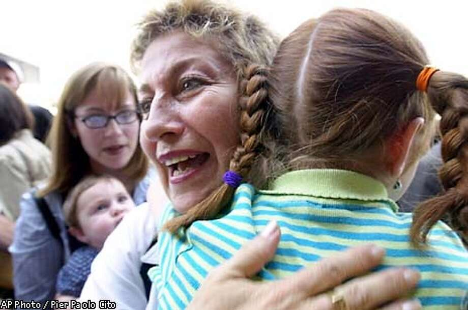 Nomi Malek, 55, welcomes her grandniece Tova, 7, as her daughter Tamar Rudy, 27, from Baltimore, Md., in the background, holds her daughter Michal, 8 months, after arriving at Tel Aviv's Ben Gurion's airport, Tuesday July 9, 2002. Defying Mideast violence, about 400 North Americans moved to Israel Tuesday to build new lives in the Jewish state. (AP Photo/Pier Paolo Cito) Photo: PIER PAOLO CITO